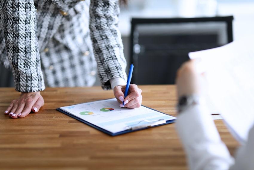 las manos de una mujer sobre una mesa tomando datos sobre un infrome de análisis de mercado